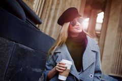 Young, hip and attractive blonde walking around the city with coffee to go, girl in a stylish hat and a gray coat royalty free stock photography