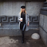 Young, hip and attractive blonde walking around the city with coffee to go, girl in a stylish hat and a gray coat Stock Image