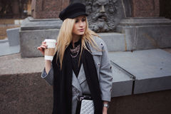 Young, hip and attractive blonde walking around the city with coffee to go, girl in a stylish hat and a gray coat Stock Images