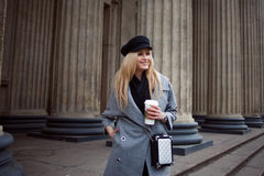 Young, hip and attractive blonde walking around the city with coffee to go, girl in a stylish hat and a gray coat Stock Photography