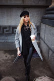 Young, hip and attractive blonde walking around the city with coffee to go, girl in a stylish hat and a gray coat Stock Photo