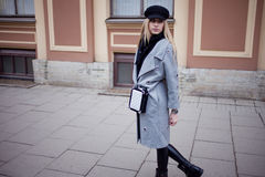Young, hip and attractive blonde walking around the city, girl in a stylish hat and a gray coat Stock Photography