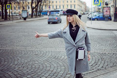 Young, hip and attractive blonde hailing taxi , girl in a stylish hat and a gray coat. Young, hip and attractive blonde walking around the city Royalty Free Stock Photo