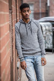 A young, hip, black man poses against a brick wall in NYC royalty free stock images