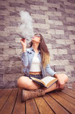 Young hip brunette sitting legs crossed on wooden surface leaning back towards stone wall, smoking e-cigarette happily Royalty Free Stock Photo