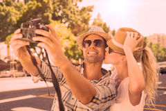Young hip couple taking a selfie Stock Illustration
