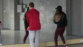 Young hip hop performers training in studio. Couple of teenagers dancing hip hop in front of mirror. Studio of contemporary dance stock footage
