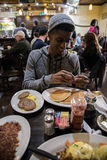 A young, hip man eats brunch at Brooklyn, NYC diner Royalty Free Stock Image