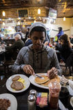 A young, hip man eats brunch at Brooklyn, NYC diner. Shot during the autumn of 2016 Stock Photos