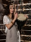 Young hippie boho woman having fun ans plays the Jamaica drum. Hippie style. On a wooden background Royalty Free Stock Photography
