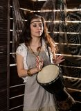 Young hippie boho woman having fun ans plays the Jamaica drum. Hippie style. On a wooden background Stock Image