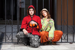 Young hippie couple sitting on the sidewalk Royalty Free Stock Photography