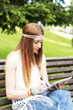 Young hippie girl laptop tablet computer in the park. Stock Image
