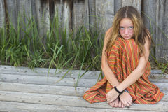 Young hippie girl sitting on the ground outdoors. Royalty Free Stock Image