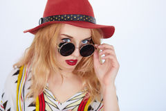 Young hippie woman in boho style clothes. Closeup fashion portrait of blonde young hippie woman in boho style clothes and sunglasses with red lips winking to Stock Photography