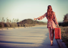 Young hippie woman hitchhiking on a road. Rear view. Young hippie woman hitchhiking on the road. Rear view Royalty Free Stock Photo