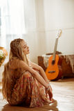 Young hippie woman. Portrait of young blonde hippie woman sitting on floor and looking away stock photo