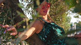 Young hippie woman with sunglasses sitting on the tree