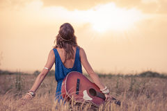 Young hippy woman with acoustic guitar enjoying the sunset. Young retro hippy styled woman with acoustic guitar in wheat field looking at sun to find inspiration Stock Photos