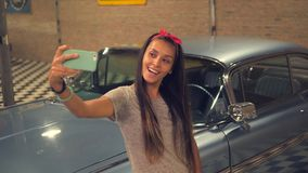 Young Hipser Pin-up Mixed Race Girl Taking Selfie with Mobile Phone at Vintage Garage and Old Car. 4K, Slowmotion. Young Hipser Pin-up Mixed Race Girl Taking stock video