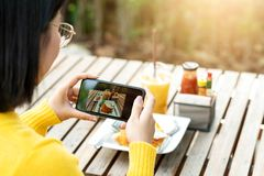 Young hipster asian blogger take photo of food, plate, healthy recipe, lunch meal, breakfast share to story in social media at. Restaurant or home. Screen royalty free stock image