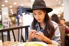 Young hipster asian woman wearing a black hat using her smartpho stock photo