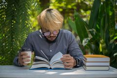 Young hipster beard man drinking coffee while reading books in h. Ome garden with nature. Education concept royalty free stock photography