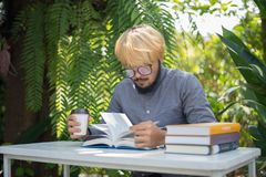 Young hipster beard man drinking coffee while reading books in h. Ome garden with nature. Education concept stock images