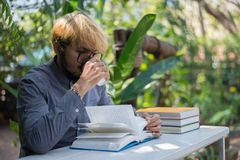 Young hipster beard man drinking coffee while reading books in h. Ome garden with nature. Education concept stock photography