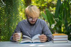 Young hipster beard man drinking coffee while reading books in h. Ome garden with nature. Education concept royalty free stock image