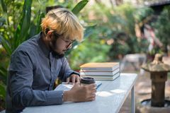 Young hipster beard man drinking coffee while reading books in h. Ome garden with nature. Education concept royalty free stock photos