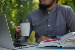 Young hipster beard man drinking coffee while reading books in h. Ome garden with nature. Education concept stock image
