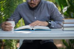 Young hipster beard man drinking coffee while reading books in h. Ome garden with nature. Education concept royalty free stock images