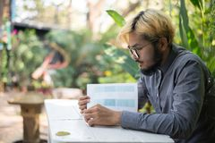 Young hipster beard man reading books in home garden with nature. Education concept royalty free stock images