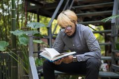 Young hipster beard man reading books in home garden with nature. Education concept stock photos
