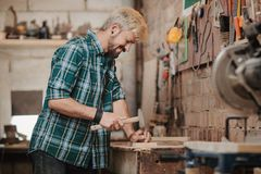 Attractive blonde young hipster bearded man by profession carpenter builder nailing wood board with hammer on a wooden. Young hipster bearded man by profession Royalty Free Stock Image