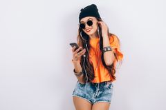 Young hipster beautiful woman in sunglasses wearing in black hat and orange T-shirt listening music in headphones near. Beautiful woman in sunglasses wearing in stock image