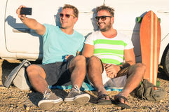 Young hipster best friends taking a selfie sitting at car stock photography