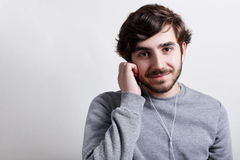 Young hipster with big dark eyes modern hairstyle and beard wearing casual grey sweater listening to the music or audiobook with h Stock Photography