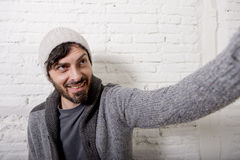 Young hipster blogger man holding off screen mobile phone shooting selfie picture or video. Young attractive man in casual clothes beanie hipster style holding Royalty Free Stock Photography