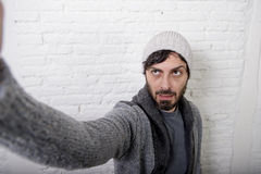 Young hipster blogger man holding off screen mobile phone shooting selfie picture or video. Young attractive man in casual clothes beanie hipster style holding Royalty Free Stock Photos