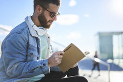 Young hipster blogger traveler in a denim jacket. Young handsome male international student dressed in trendy casual outfit preparing for upcoming test in Royalty Free Stock Images