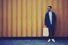 Young hipster blogger traveler in a denim jacket holding bag with copy space for your brand name. Handsome hipster guy shopper dressed in trendy coat and eyewear stock photo