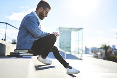 Young hipster blogger traveler in a denim jacket using modern touchpad and free wireless internet connection Royalty Free Stock Image