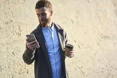 Young hipster blogger traveler in a denim jacket using navigator application on smartphone connected to fast 4G internet Royalty Free Stock Photos