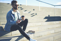 Young hipster blogger traveler in a denim jacket via smartphone and 5G wireless connection Royalty Free Stock Image