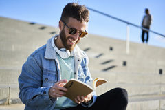 Young hipster blogger traveler in a denim jacket working outdoors to inspire by weather. Young male creative manager of event agency feeling happy after Royalty Free Stock Photos