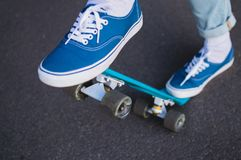 Penny skateboard commute hipster transport solutions. Young hipster in blue jeans and canvas scateshoes standing on the blue penny board and ready for tricks Stock Photography