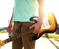 Young hipster in a blue t-shirt with a guitar stands on the road in contrast to sunlight and glare, a summer day outdoors. Man, standing, caucasian, musician royalty free stock photography
