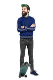 Young hipster in blue tracksuit jacket and baseball cap on skateboard looking away smiling Stock Photos